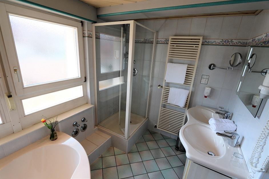 Großes Badezimmer mit zwei Waschbecken, Dusche und Eckbadewanne