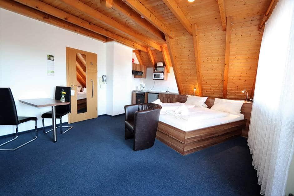 Appartement Städtleblick mit schräg stehendem Doppelbett und kleiner Küchenzeile