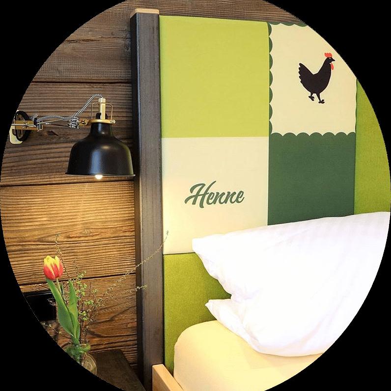 Kopfteil mit Hahn und Henne des Doppelbettes in der Ferienwohnung Hahn und Henne