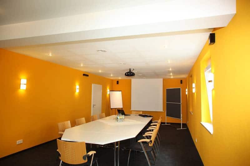"""Seminarraum """"Brandenkopf"""" mit Beamer an der Decke, Pinwand, Flipchart und großer Leinwand"""