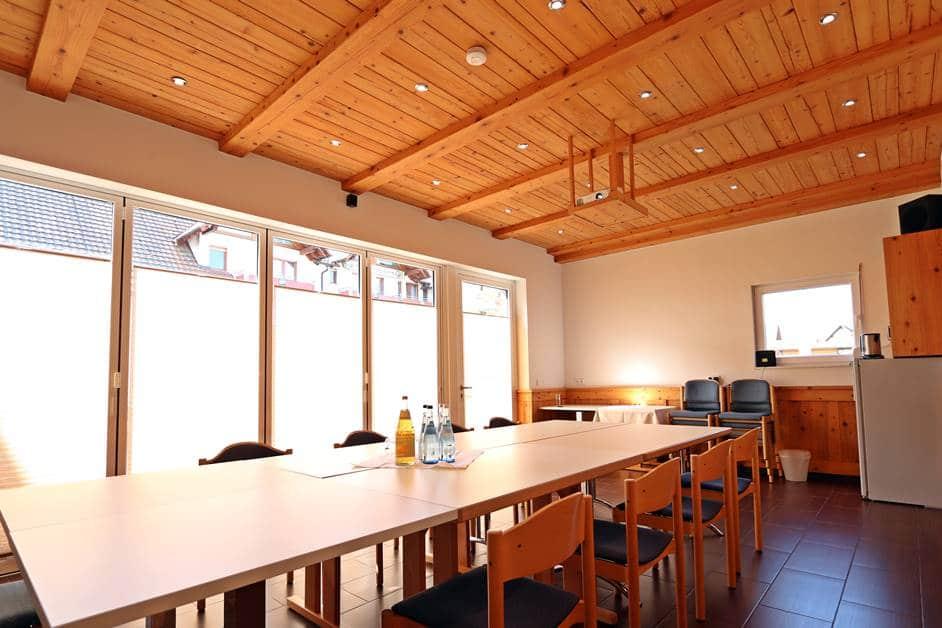 """Seminarraum """"Harmersbach"""" mit Blockbestuhlung, Beamer an der Decke und großer Fensterfront zur Sommerterrasse"""