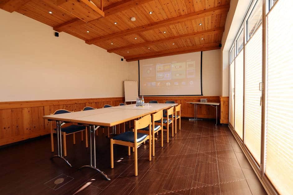 """Seminarraum """"Harmersbach"""" mit Blick über die Blockbestuhlung zur großen Leinwand"""
