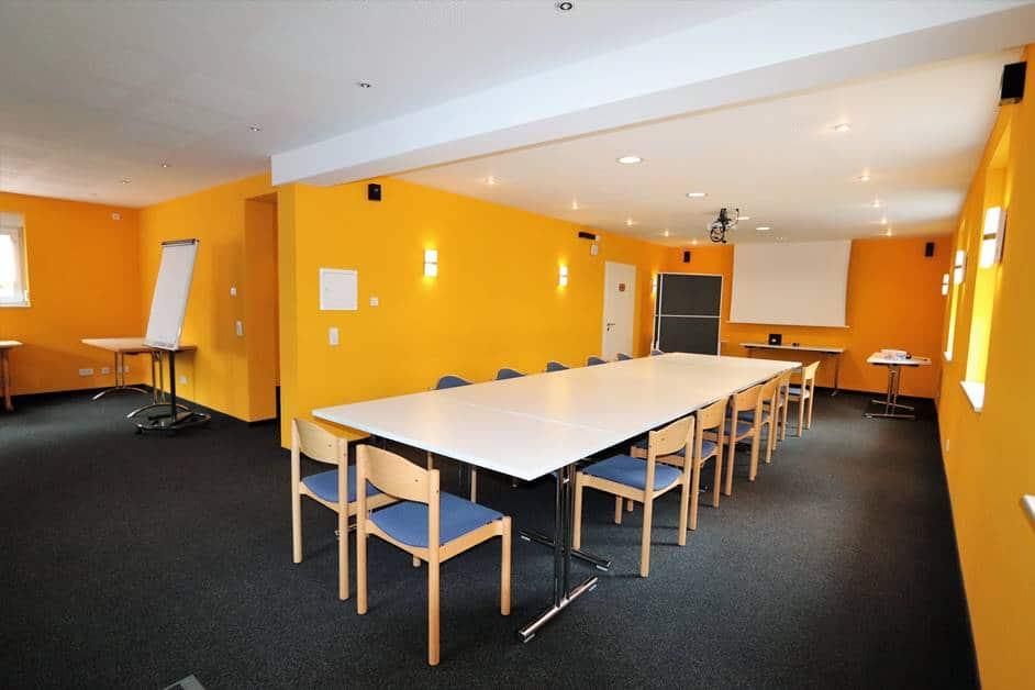 """Seminarraum """"Brandenkopf"""" in Haus Sonnenschein mit Blockbestuhlung und Beamer mit Leinwand"""