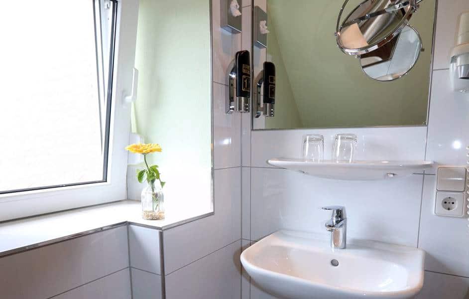 Helles Badezimmer mit großem Spiegel, Waschbecken und großem Fenster