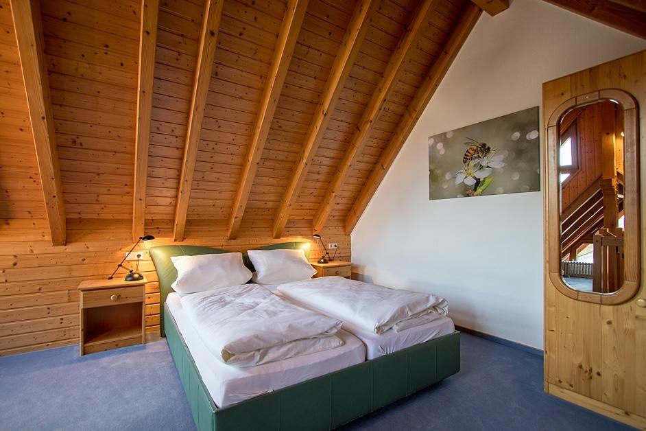 """Doppelbett und großes Bienenbild auf Leinwand in der Ferienwohnung """"Bienenstock"""""""