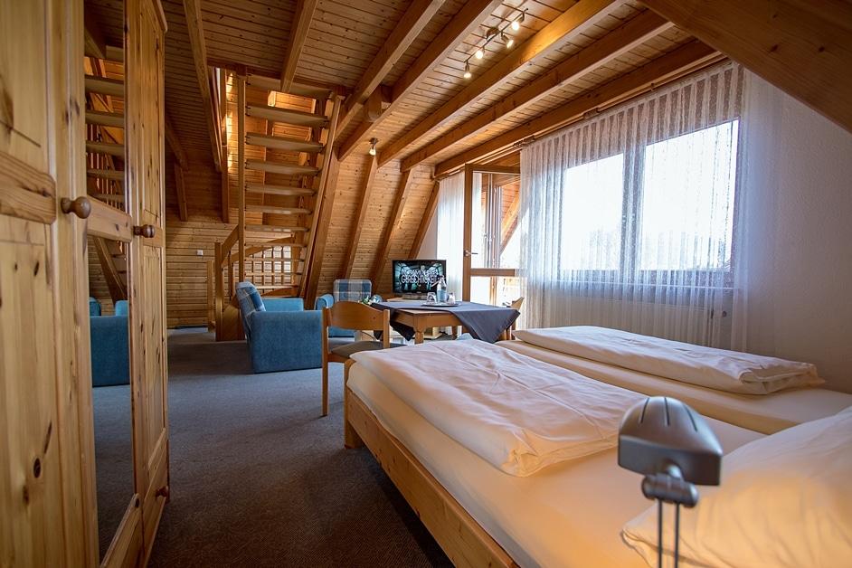 Blick über das Doppelbett in den Wohnbereich und Balkon
