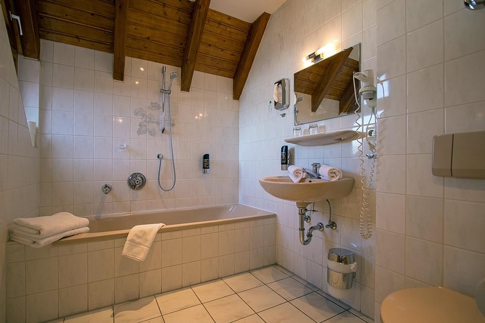 Großes Badezimmer mit Badewanne und WC